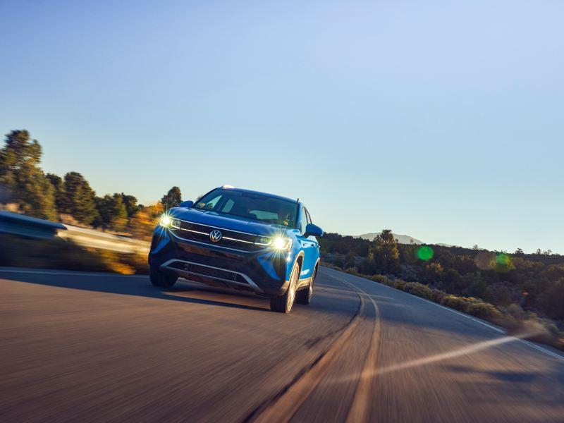Vue avant d'un Taos de Volkswagen s'approchant graduellement, le jour, sur une route déserte.