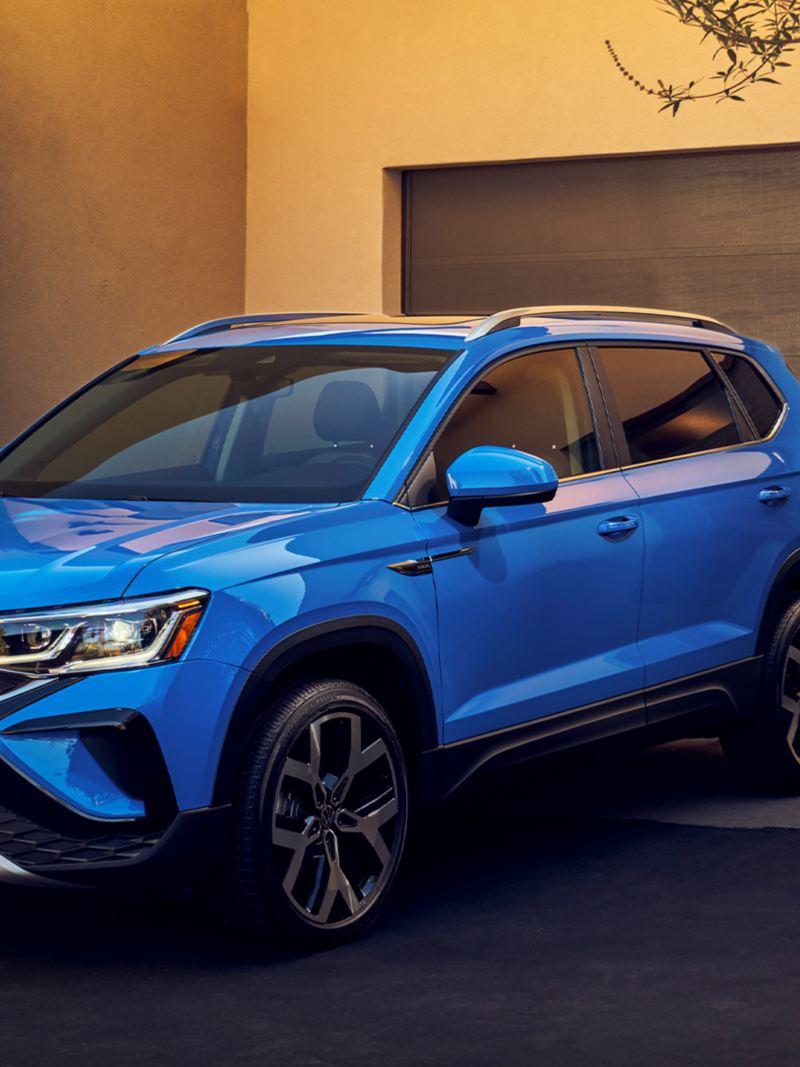 Vue de profil d'un Taos bleu de Volkswagen garé dans l'entrée d'une résidence en journée.