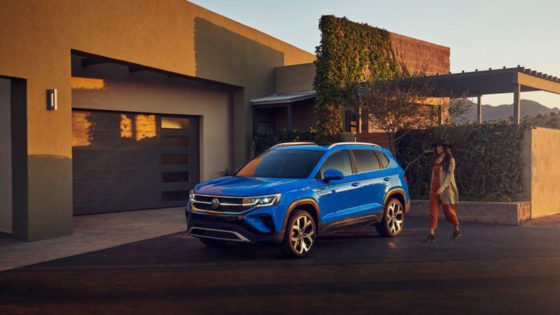Vue de profil d'un Taos bleu de Volkswagen garé devant une résidence à la tombée du jour. Une femme se diige vers celui-ci.