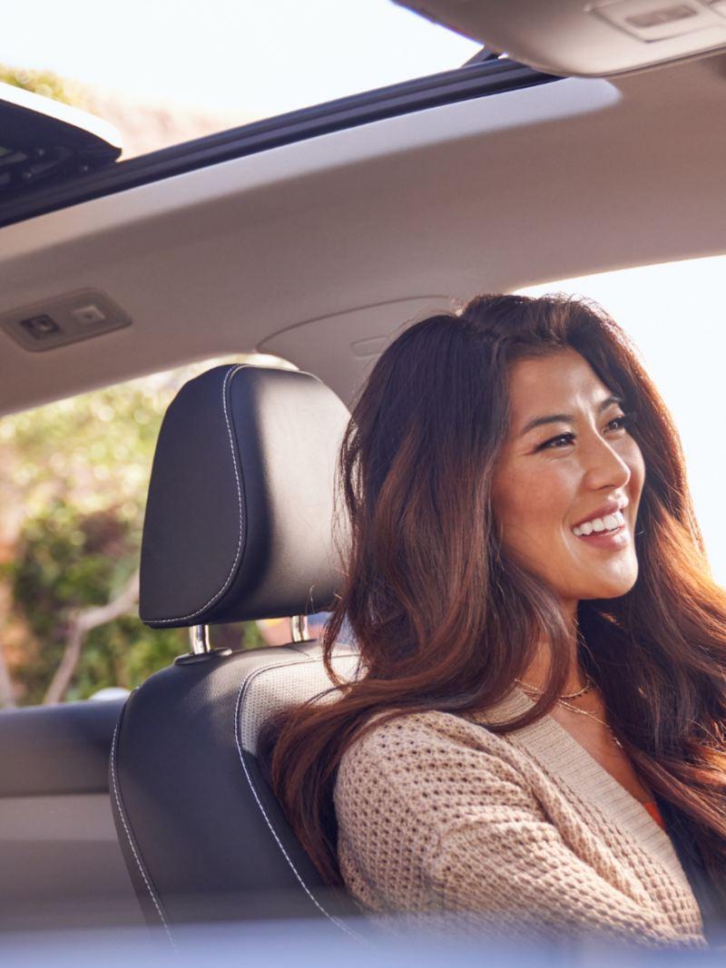 Vue de l'intérieur du Taos de la fenêtre de la place du passager, d'une femme souriant assise à la place du conducteur.