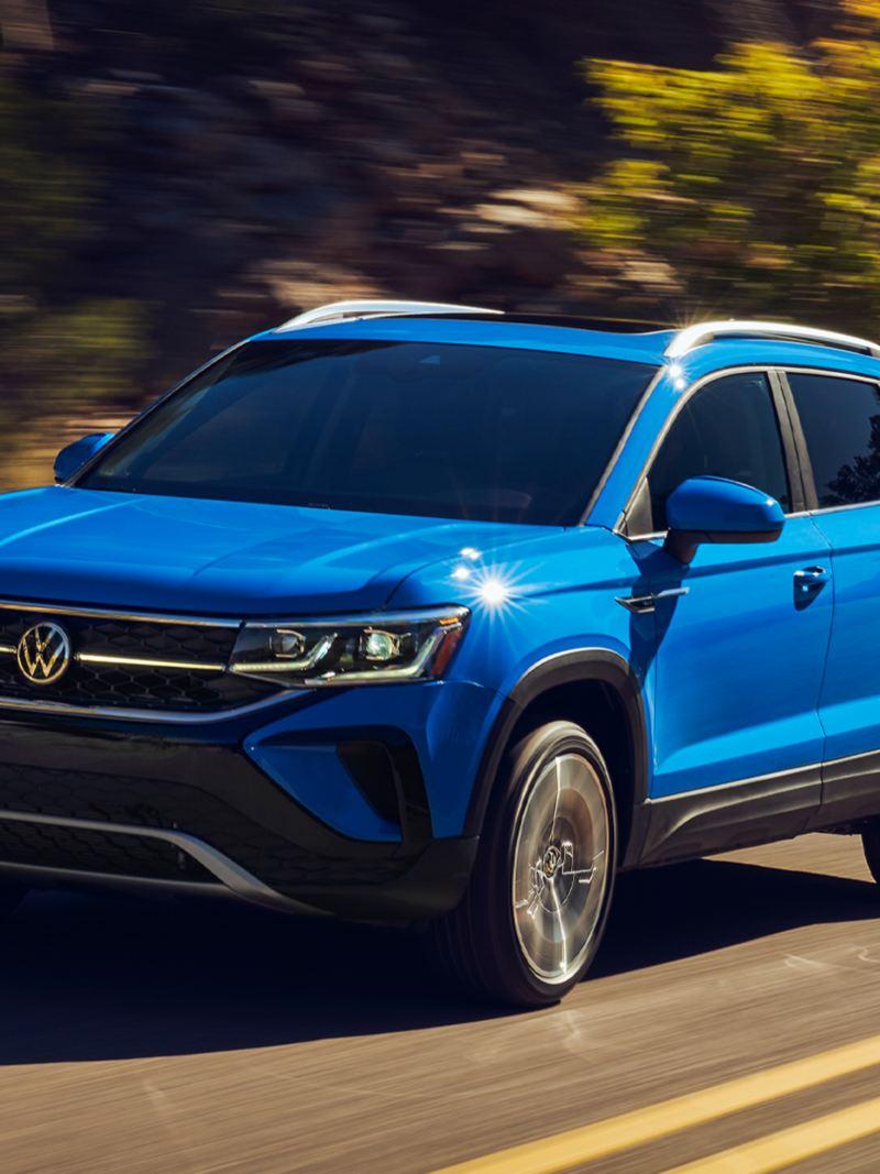 Une vue de face d'un Taos bleu de Volkswagen roulant sur une route sinueuse.