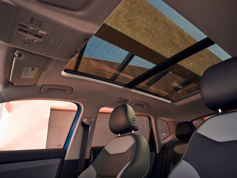 Vue de l'habitacle avant du Volkswagen Taos et de son toit ouvrant panoramique.