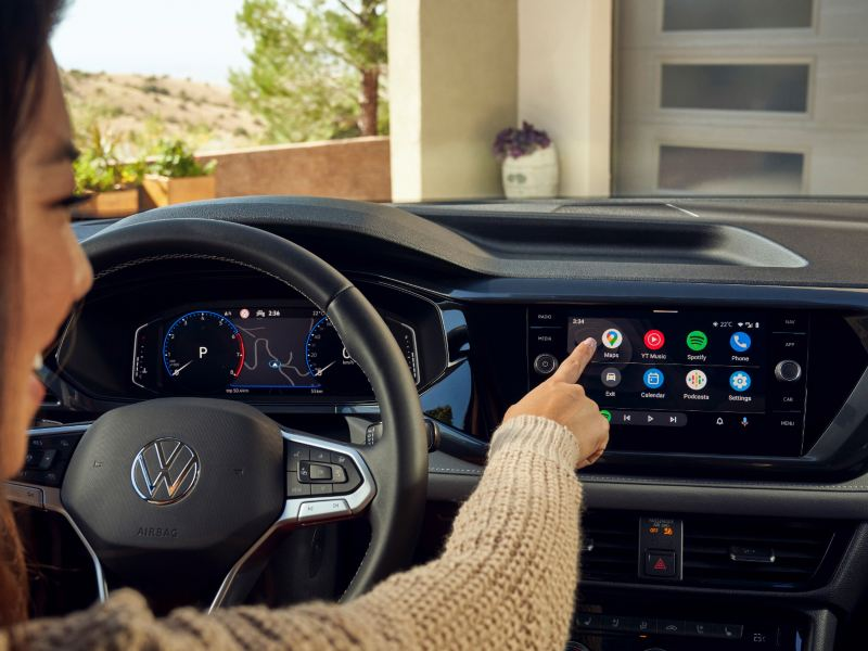Une femme au volant touche l'écran tactile d'un Taos de Volkswagen.