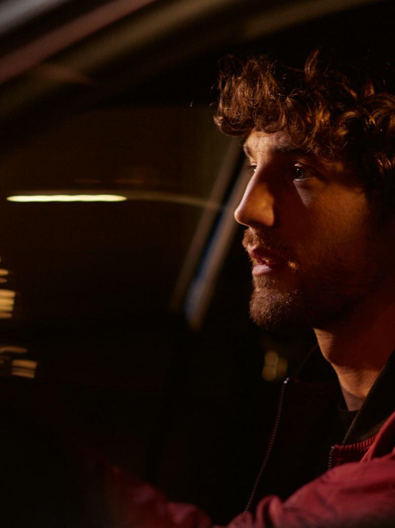Uomo mentre guida una VW di notte