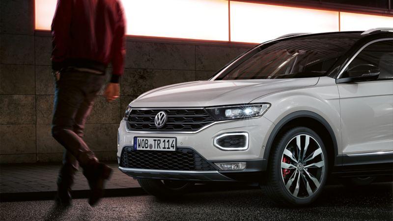 Ein Fußgänger überquert die Straße vor einem Volkswagen