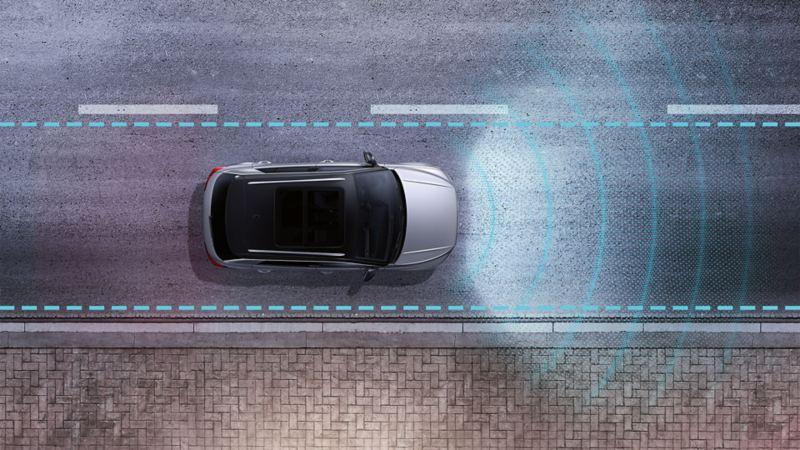 Una VW T-Roc di notte su una strada vista dall'alto. Il funzionamento dei sensori dell'assistenza per il mantenimento della corsia Lane Assist è rappresentato da linee