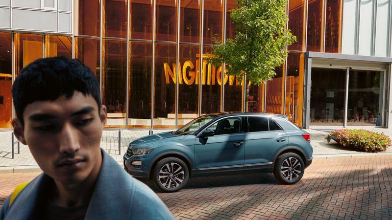 Parkerende T-Roc IQ.DRIVE in de achtergrond; op de voorgrond een man.