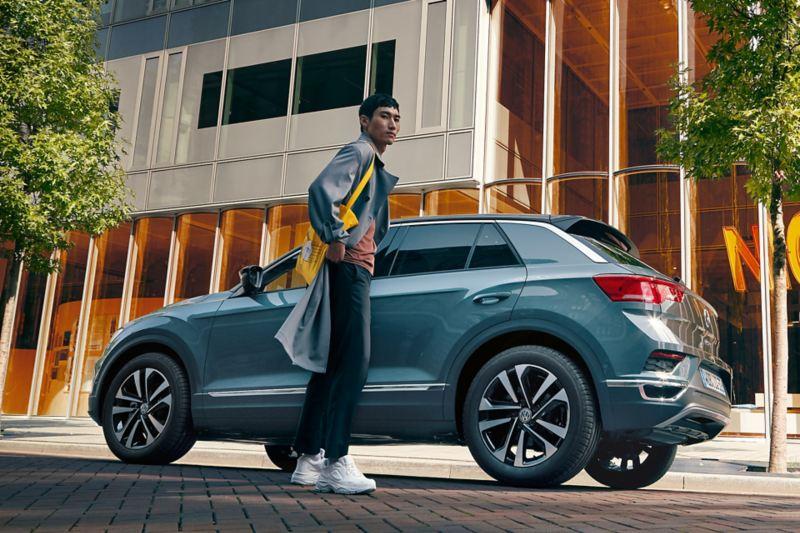 Un homme se tient devant un T-Roc IQ.DRIVE.