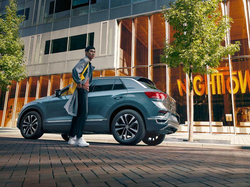 Volkswagen henkilöauto kuvattuna kadulla alaviistosta, auton edustalla seisoo henkilö