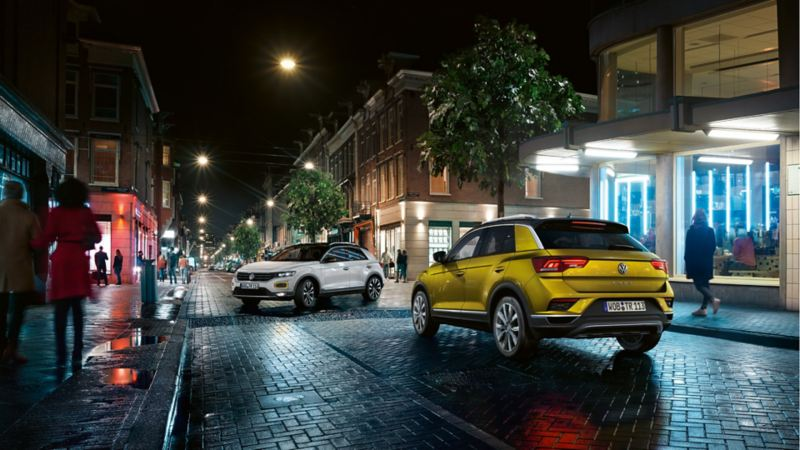 Volkswagen T-Roc Style e Volkswagen T-Roc Advanced in città di notte ad un incrocio a T