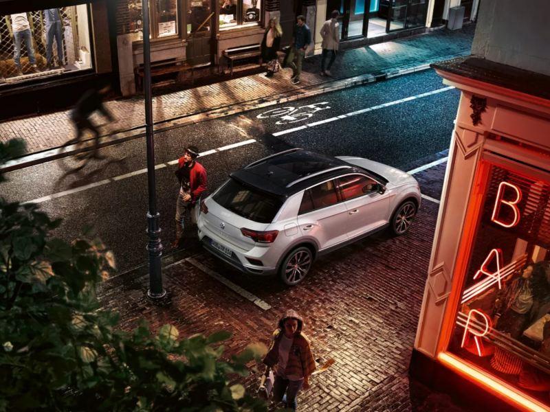 T-Roc Sport sur une place de stationnement devant un bar; le chauffeur contourne le véhicule