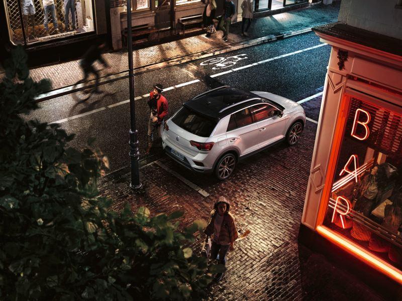 T-Roc Sport estacionado em frente a um bar; o condutor contorna a traseira do automóvel.