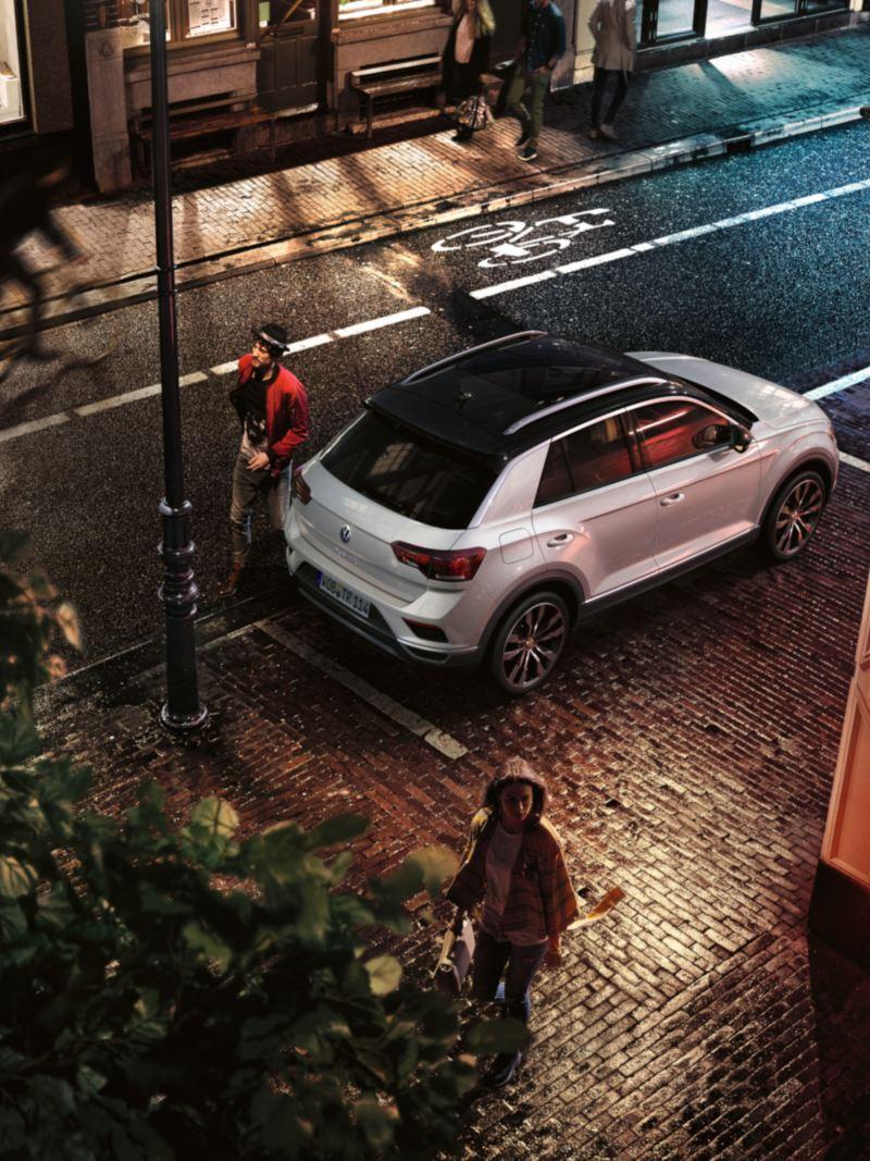La T-Roc Sport in un parcheggio davanti a un bar; il conducente passa vicino alla coda del veicolo