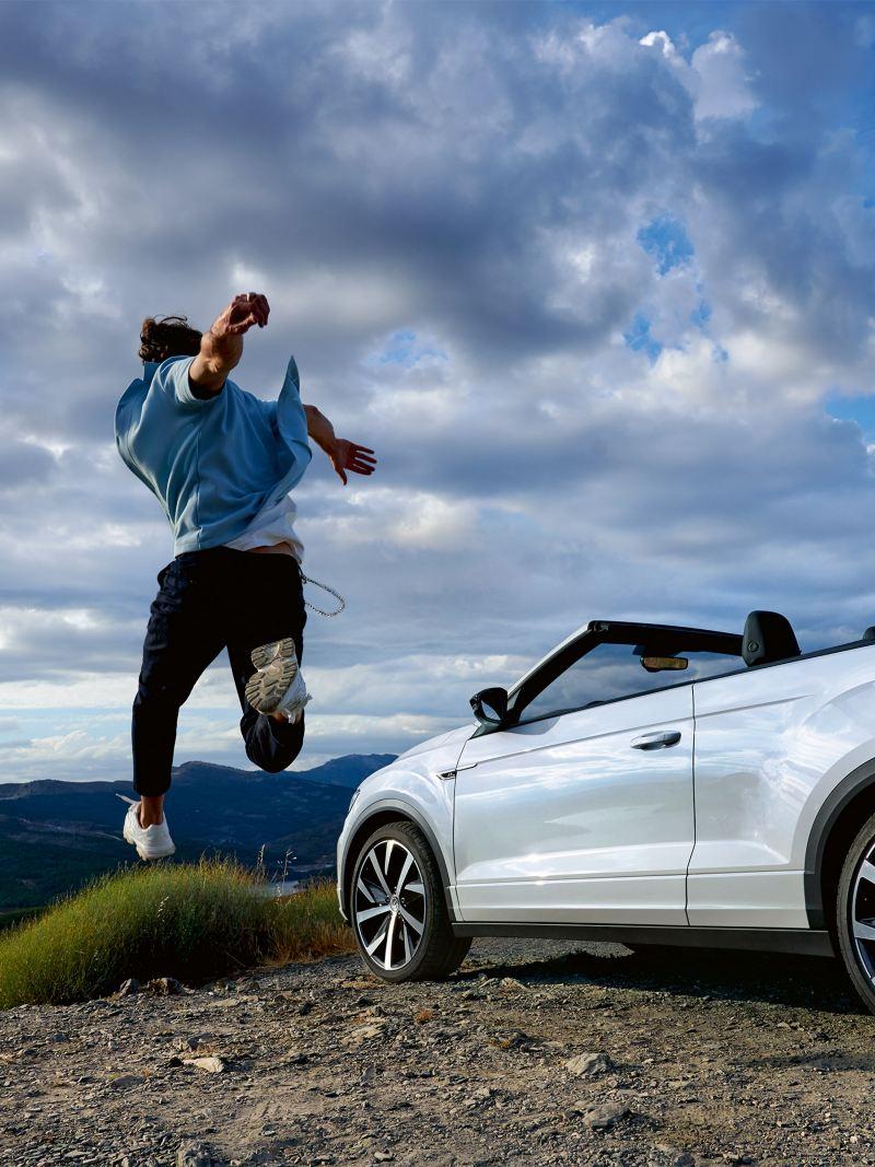 Mann springt neben T-Roc Cabrio in die Luft