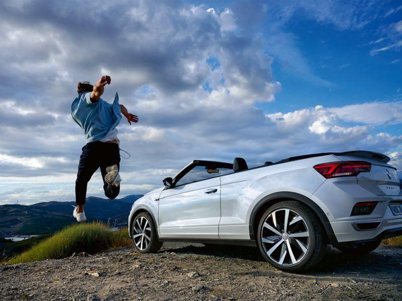 Mann springt neben VW T-Roc Cabrio in die Luft