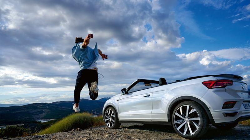 Mann springt in die Luft, neben ihm parkt ein T-Roc Cabrio.