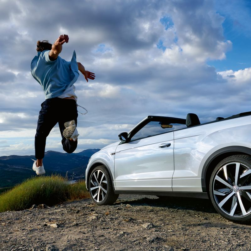 Uomo che salta vicino alla T-Roc Cabriolet Volkswagen