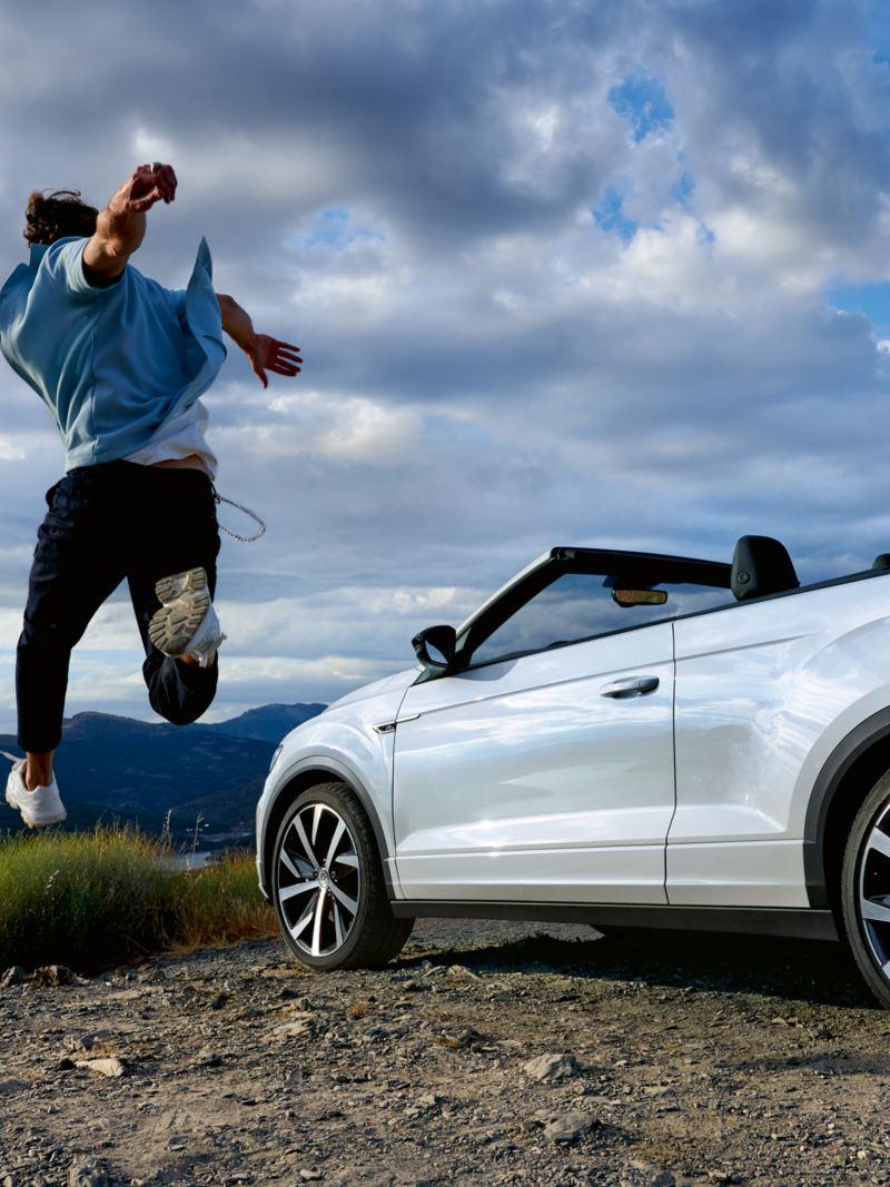 Ragazzo che salta, VW T-Roc Cabriolet parcheggiata