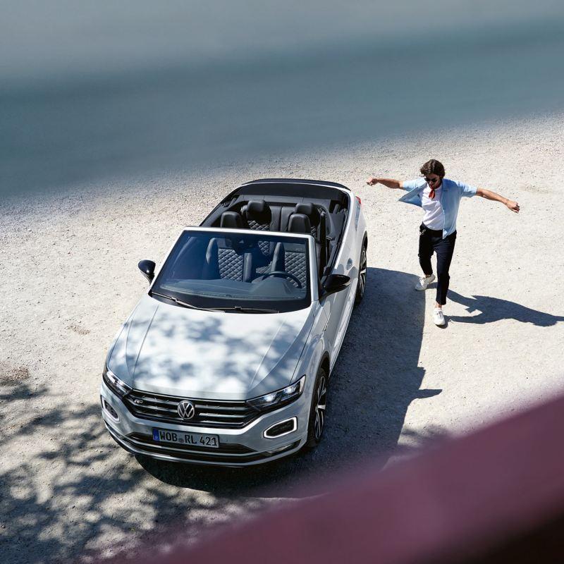 Uomo si muove vicino a VW t-roc cabriolet ferma in spiaggia