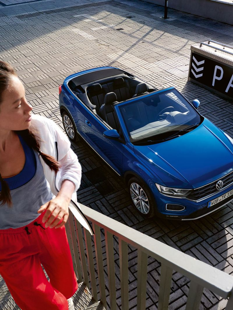 Woman running up stairs, VW T-Roc Cabriolet parked in the background