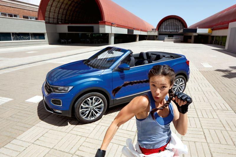 Frau in sportlicher Pose vor dem VW T-Roc Cabriolet