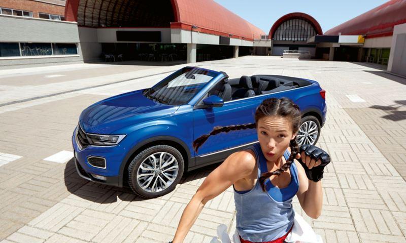 Ragazza salta davanti a VW T-Roc Cabriolet parcheggiata