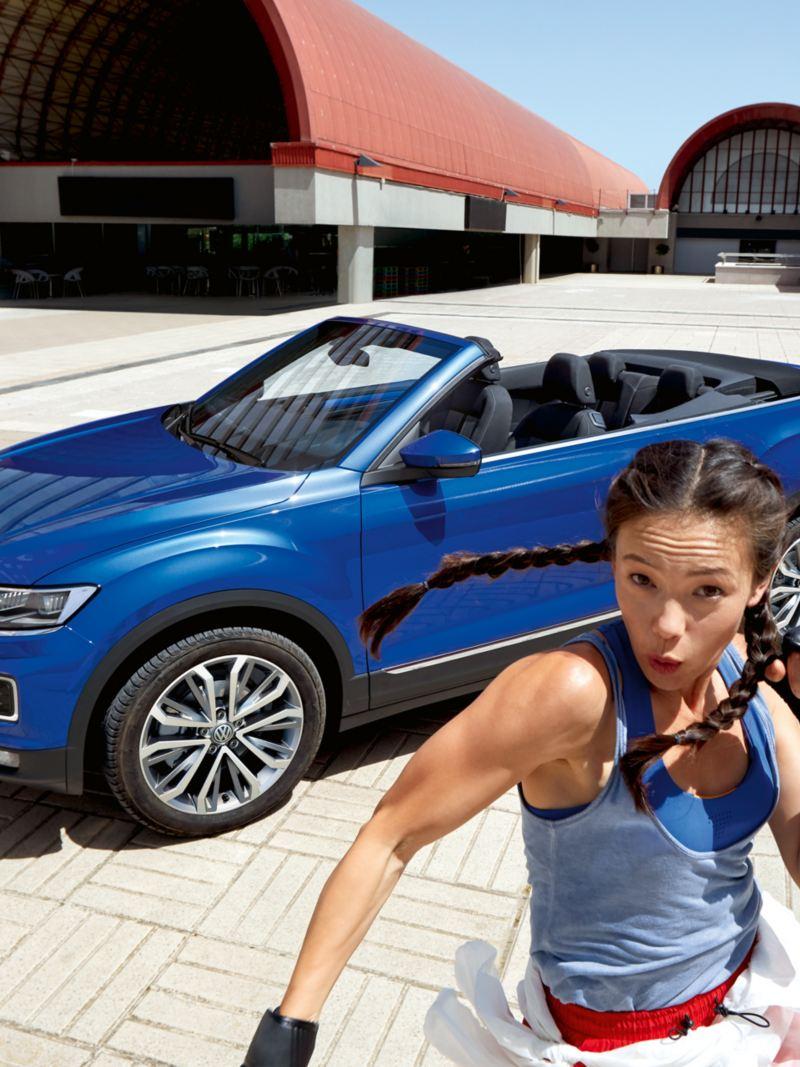 Une femme pose de façon sportive devant le VW T-Roc Cabriolet