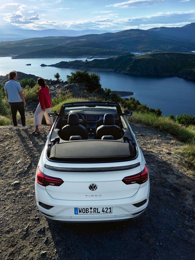 Une VW T-Roc Cabrio fait face à un paysage, un couple est debout à côté de la voiture.