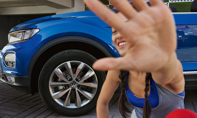 Woman is in front of the VW T-Roc Cabriolet