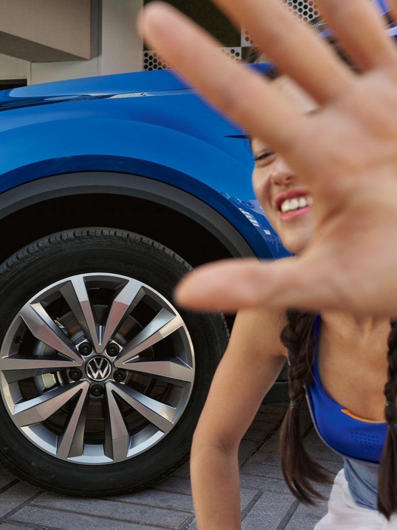 Μια γυναίκα στέκεται μπροστά από ένα volkswagen T-Roc Cabriolet