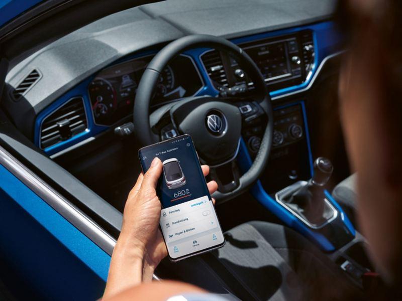 Ein Mann steht neben VW T-Roc Cabriolet und öffnet VW Connect App