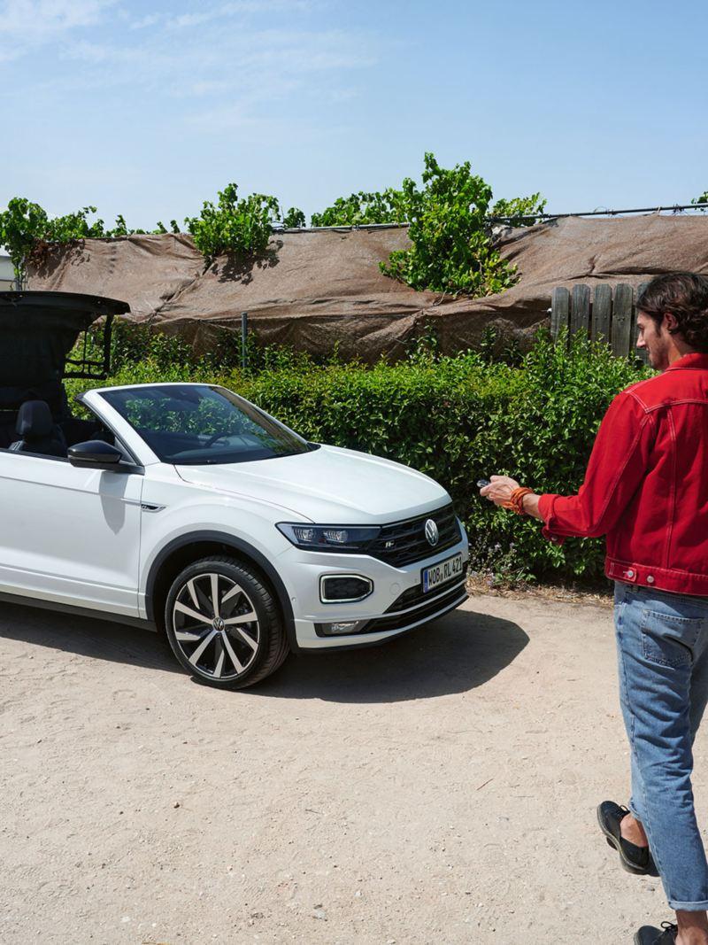Mann öffnet Stoffverdeck vom VW T-Roc Cabriolet