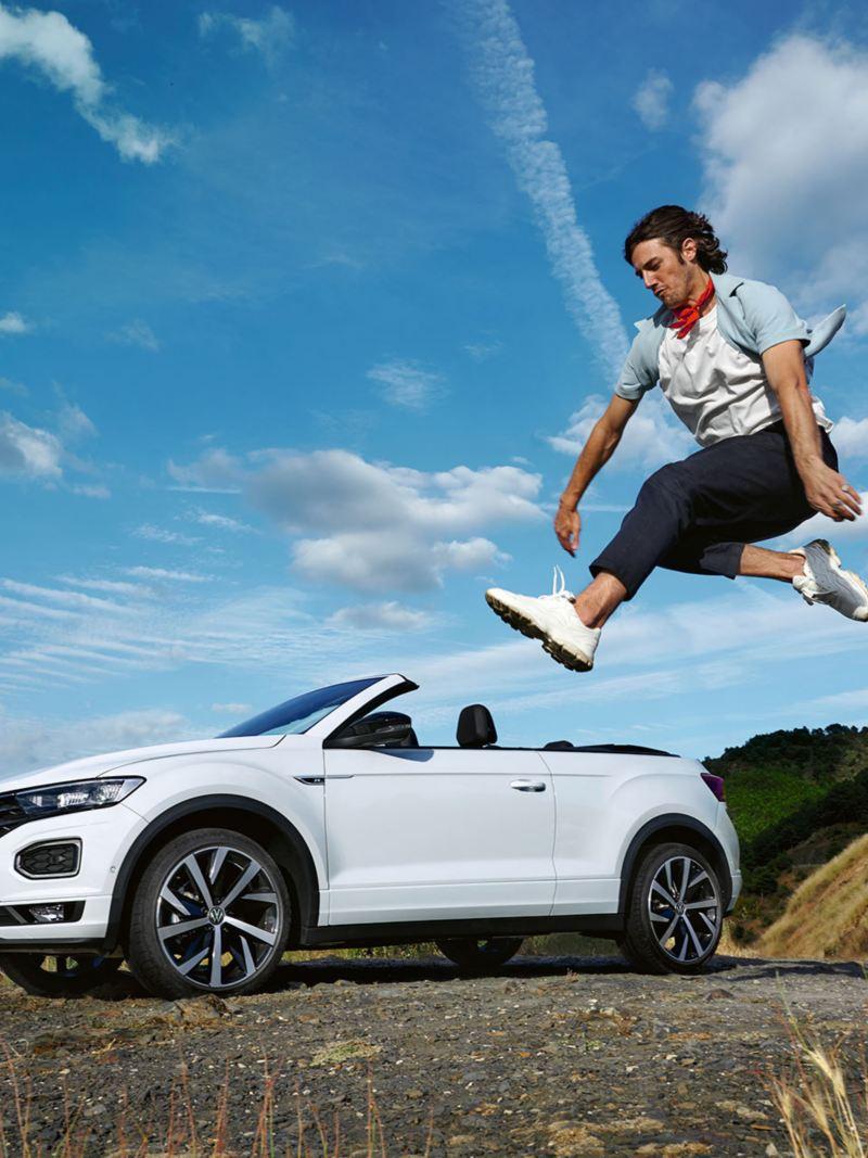 VW T-Roc Cabriolet en arrière-plan, homme fait de l'exercice devant