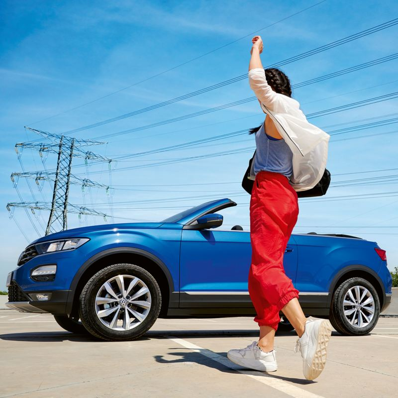 Woman is dancing next to VW T-Roc Cabriolet
