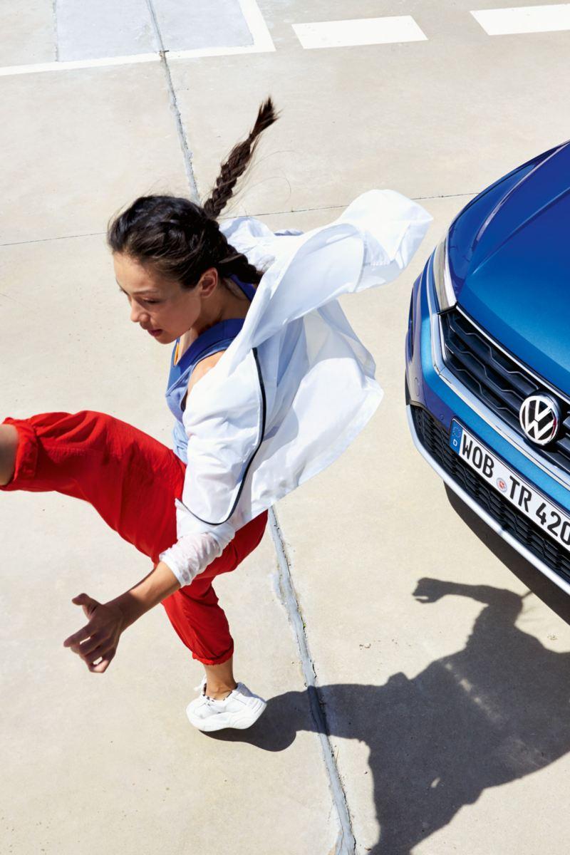 Eine Frau macht einen 'Air Kick' vor dem T-Roc Cabriolet