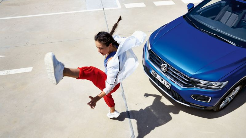 A woman doing an 'Air Kick' in front of the T-Roc Cabriolet