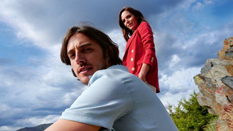 Mann sitzt auf Holzzaun, Frau steht daneben, beide schauen in die Ferne