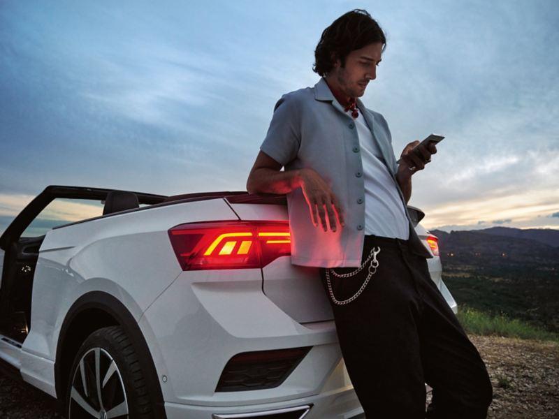 Man steht mit Handy hinter dem VW T-Roc Cabriolet