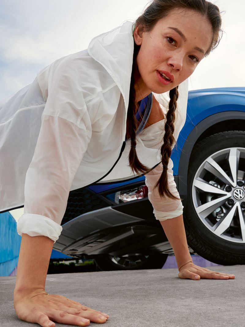 Ragazza fa un piegamento davanti a VW T-Roc Cabriolet blu