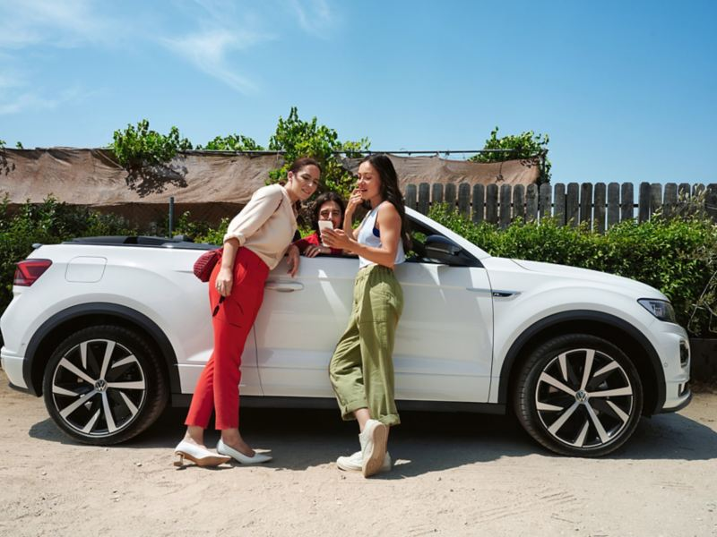 Man and women play mobile phone in front of T-Roc Cabriolet
