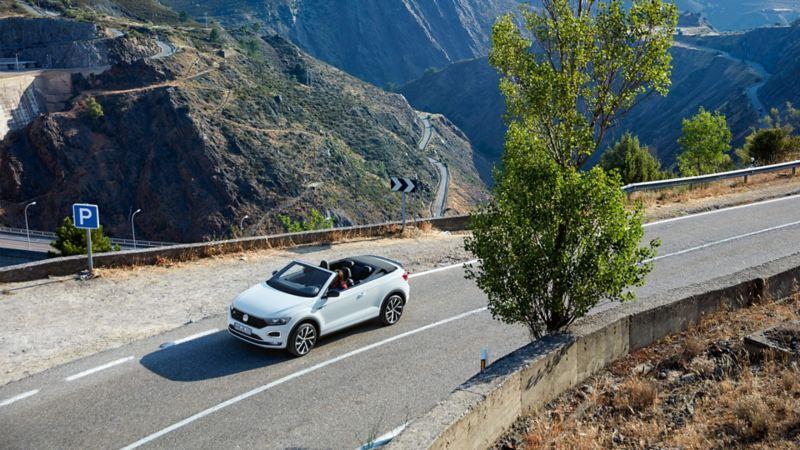 Una Volkswagen cabrio mentre percorre una strada di montagna.
