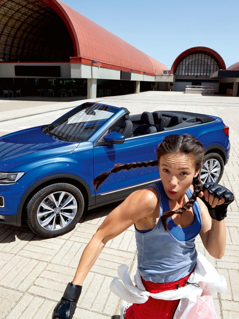 Ragazza sportiva si allena davanti a VW t-roc cabriolet ferma in un piazzale pavimentato