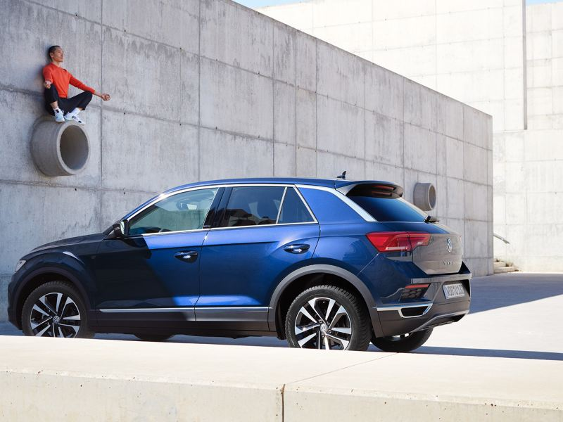 VW T-Roc UNITED 3/4 rear view, man sitting on pipe on wall