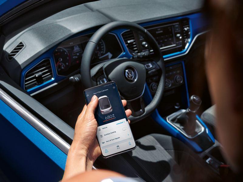 Ένας άντρας στέκεται δίπλα από το volkswagen T-Roc Cabriolet και ανοίγει την εφαρμογή VW Connect