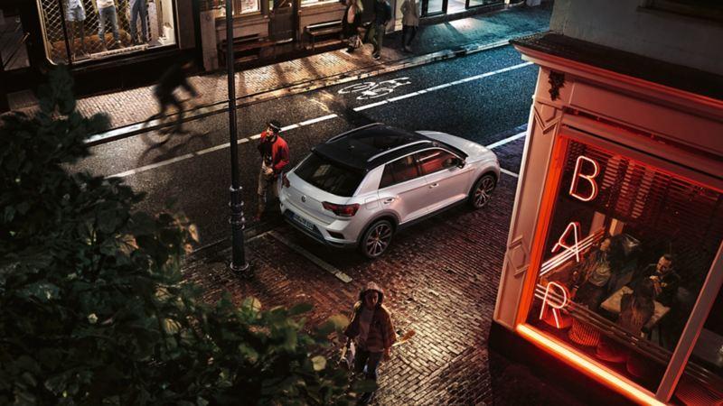 Volkswagen T-Roc Advanced parcheggiata davanti a un bar; il conducente gira intorno al lato posteriore