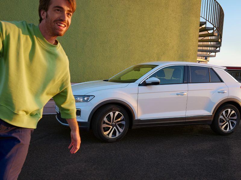 Weißer VW T-Roc ACTIVE steht vor einer gelben Wand in urbaner Umgebung.