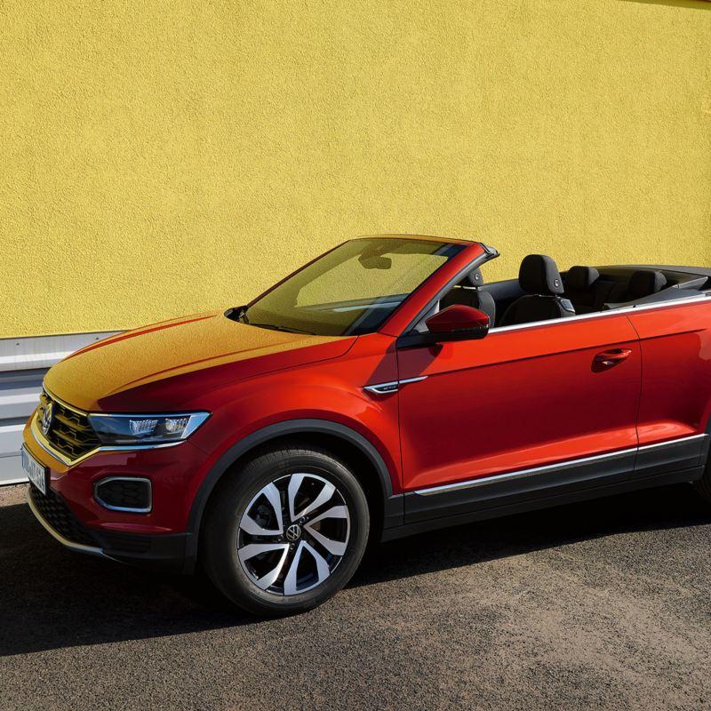 Roter VW T-Roc Cabriolet ACTIVE mit geöffneten Verdeck parkt vor einer gelben Wand in urbaner Umgebung.