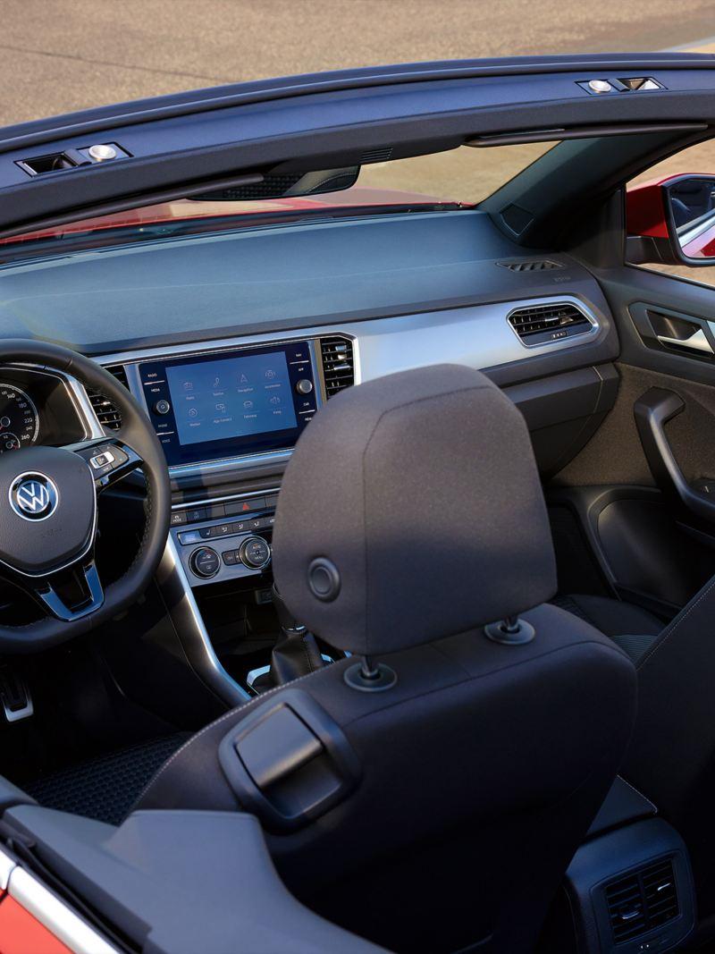 Roter VW T-Roc Cabriolet ACTIVE von oben mit geöffnetem Verdeck betrachtet. Blick auf Sitze, Multifunktionslenkrad, Pedalkappen und Cockpit.