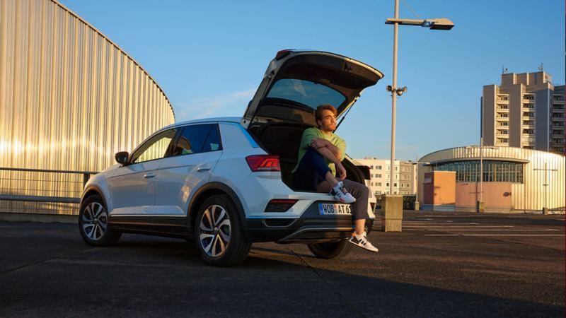 Weißer VW T-Roc ACTIVE parkend in urbaner Umgebung mit geöffnetem Kofferraum.
