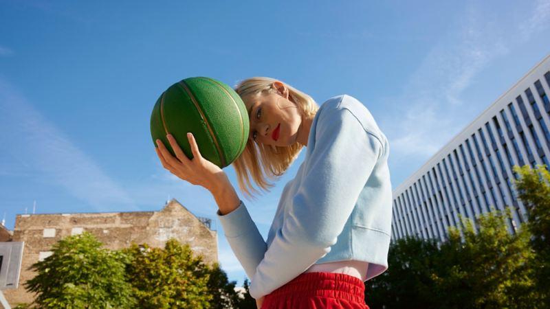 Frau mit Basketball in der Hand in urbaner Umgebung mit blauem Himmel im Hintergrund.